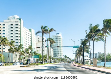 Miami Beach, USA - May 5, 2018: Collins Avenue and 4600 block street intersection with many apartment, condos, condominiums complex buildings, bay, boat, windy, palm trees