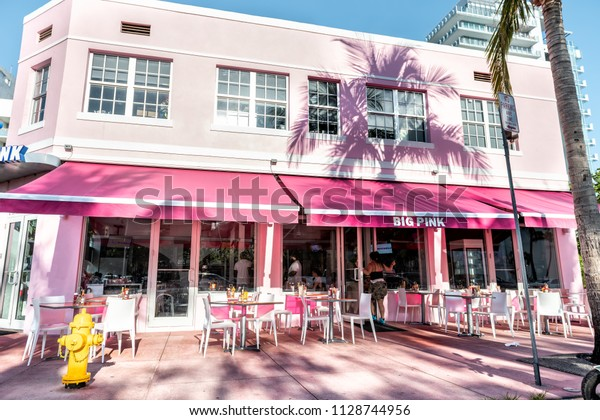 Miami Beach, USA - May 5, 2018: Big Pink diner, restaurant, cafe at Ocean Drive Art Deco district on sunny day with outside sitting empty area, tables, chairs