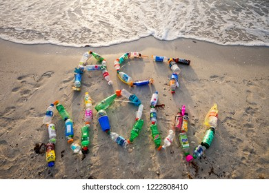 MIAMI - CIRCA AUGUST, 2018: Ocean plastic pollution awareness message spelling out Act Now made from consumer drink and water bottles found on the beach.