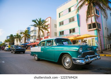 MIAMI - CIRCA JANUARY, 2018: A line of classic cars stand parked on front of iconic colorful Art Deco architecture on Ocean Drive.