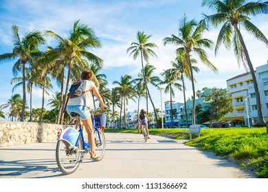 MIAMI - CIRCA JUNE 2017: Young woman rides bike along the Miami Beach promenade with backdrop of iconic art-deco buildings and palm trees of Ocean Drive