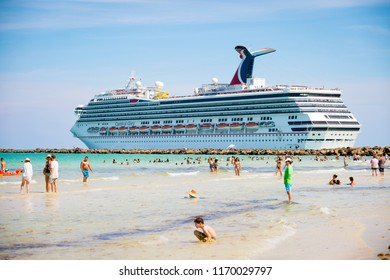MIAMI - CIRCA JUNE, 2018:  Carnival Glory cruise ship leaves port and passes people paddling in shallow waters of  South Beach.