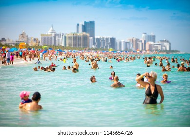 MIAMI - CIRCA JUNE, 2018: Crowds of people enjoy the sea and sand of South Beach on a hot summer weekend.
