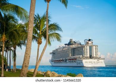 MIAMI - CIRCA JUNE, 2018: MSC Seaside cruise ship passes South Beach palm trees as it leaves port.