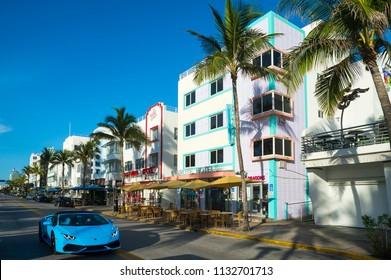MIAMI - CIRCA JUNE 2018: Restaurants on the tourist strip of Ocean Drive stand ready for morning customers in South Beaches a sports car drives past.