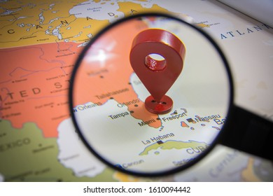 Miami city in focus through magnify glass on United states of America map with a location GPS icon world map
