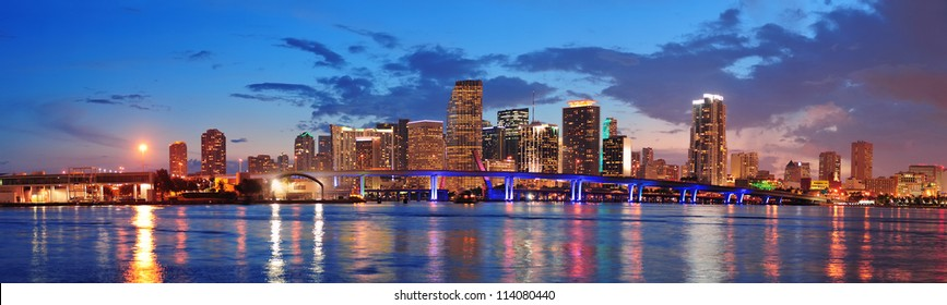 Miami City Skyline Panorama At Dusk With Urban Skyscrapers And Bridge Over Sea Reflection