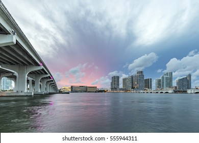 Miami city skyline panorama at dusk with urban skyscrapers and bridge