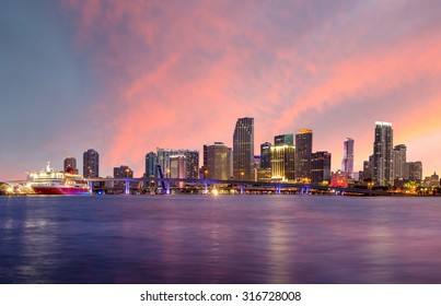 Miami city skyline panorama at twilight with urban skyscrapers and bridge USA