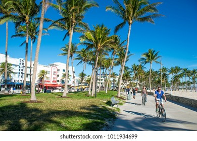MIAMI - DECEMBER 27, 2017: Cyclists and joggers share the morning beachfront boardwalk promenade at Lummus Park in South Beach.