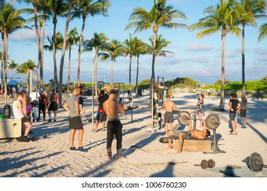 MIAMI - DECEMBER 27, 2017: Muscular young men work out at the outdoor fitness station known locally as Muscle Beach South Beach, which attracts onlookers passing on the Lummus Park promenade.