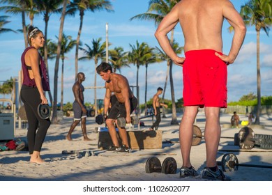 MIAMI - DECEMBER 29, 2017: Muscular young men and women work out in the outdoor gym known as Muscle Beach in Lummus Park.