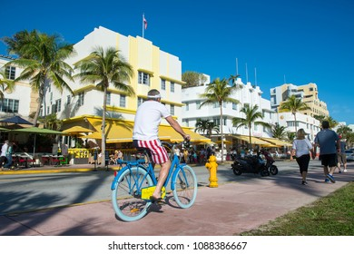 MIAMI - DECEMBER 29, 2017: Visitors walk with their bicycles past the iconic Art Deco architecture of Ocean Drive.