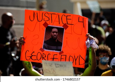 Miami Downtown, FL, USA - MAY 31, 2020: George Floyd death: people are protesting and rioting. Justice for George Floyd poster. People took to the streets against cruelty