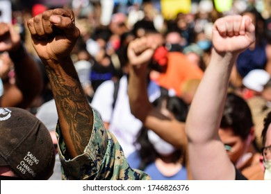 Miami Downtown, FL, USA - MAY 31, 2020: White and black hands together at the demonstration. Black Lives Matter. Many american people went to peaceful protests in the US against the George Floyd death