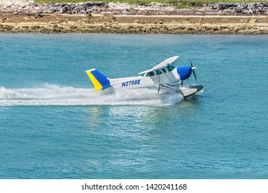 Miami, FL, United States - April 20, 2019: The Seaplane Cessna 172N Skyhawk takes off in the Miami Main channel next to the cruise port of Miami, Florida, United States of America.