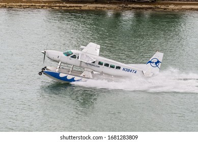 Miami, FL, United States - April 20, 2019: The Seaplane Cessna Cessna 208B Grand Caravan landing in the Miami Main channel next to the cruise port of Miami, Florida, United States of America.