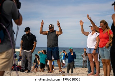 MIAMI, FL, UNITED STATES - JUNE 24, 2021: People prays near a partially collapsed building in Surfside North of Miami Beach.