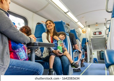Miami, FL / USA - 2/8/2020: Portuguese lady mother woman and small young latino boy child seated inside a Tri-Rail light rail train to Fort Lauderdale Broward County, Palm Beach and Miami Dade