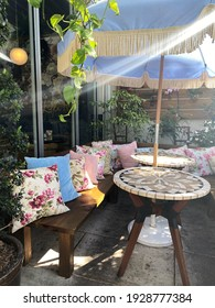 Miami, Fl, USA: March 3, 2021: Vintage outdoor patio decertations for a tea party at a bridal shower. Sun shining through. Fancy floral pillows in an upscale restaurant in Miami called Little Hen.