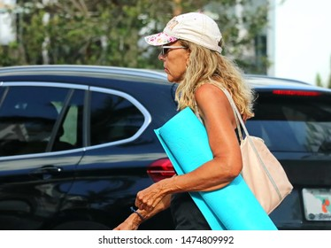 Miami, FL / USA - May 30, 2018: Woman holds yoga mat and walks to her class