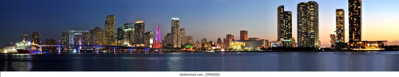 Miami, Florida, 5. April 2014 - Miami city skyline panorama at dusk with urban skyscrapers and bridge over sea.