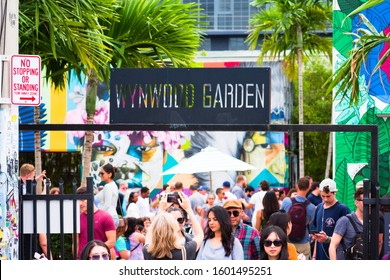 Miami, Florida - December 29, 2019: Wide view of crowd of people walking in Wynwood Garden at colorful contemporary Wynwood Walls outdoor art district graffiti mural painting museum