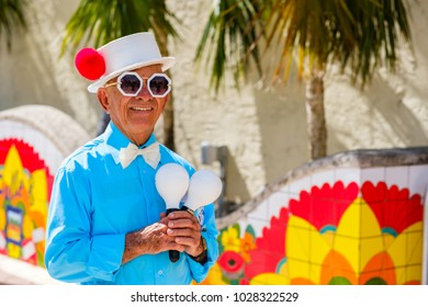 Miami, Florida - February 12, 2018: Unidentified elderly street performer in costume holding maracas along Southwest eight street in popular Little Havana.