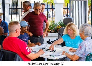 Miami, Florida - February 12, 2018: Unidentified elderly individuals play the domino game in the historic Domino Park in popular Little Havana.