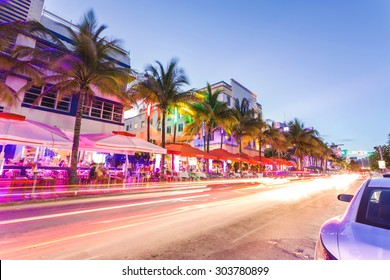 MIAMI, FLORIDA - JUNE 21, 2015: Cars speed down Ocean Drive. The road is the main thoroughfare through South Beach, Miami. Ocean Drive scene at night lights, cars and people having fun, Miami beach.
