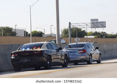MIAMI, FLORIDA - MARCH 27, 2019: Florida State Trooper stopped car in South Miami.The Florida Highway Patrol is a division of the Florida Department of Highway Safety and Motor Vehicles