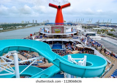 Miami, Florida - March 29 2014: Passengers onboard the Carnival Liberty Cruise Ship in Miami, on the top open decks with water slide and pool. Miami city skyline in background.