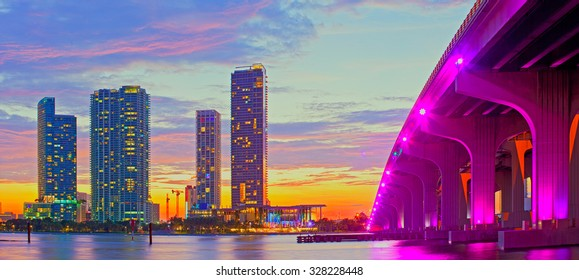 Miami Florida at sunset, colorful skyline of illuminated buildings and Macarthur causeway bridge