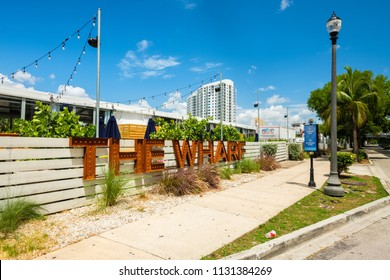 Miami, Florida USA - July 9, 2018: Scenic downtown Miami cityscape along the Miami River with the popular Wharf, a pop-up event space with music and food and beverage kiosks.