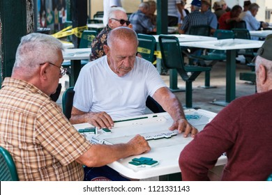 Miami, Florida USA - June 26, 2018: Elderly individuals play the domino game in the historic Domino Park in popular Little Havana.