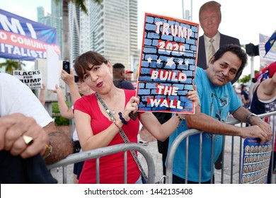 Miami, Florida/USA-June 26, 2019: Trump protesters and supporters outside of the Adrienne Arsht Center before a Democratic presidential debate waving signs about building the wall, Medicare, and Trump