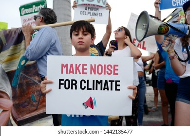 Miami, Florida/USA-June 26, 2019:  Young boy and a coalition of environmental groups, march & rallied outside the Democratic Presidential debate, with signs calling for specific climate change debates