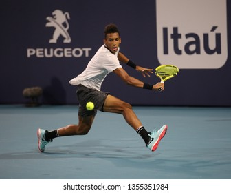 MIAMI GARDENS, FLORIDA - MARCH 27, 2019: Professional tennis player Felix Auger-Aliassime of Canada in action during his quarterfinal match at 2019 Miami Open at the Hard Rock Stadium in Miami Gardens