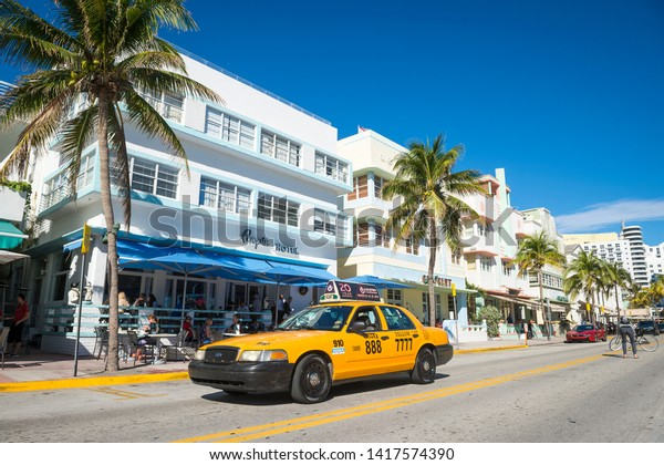 MIAMI - JANUARY 12, 2018: A taxi drives past restaurants on the tourist strip of Ocean Drive ready for morning customers in South Beach.