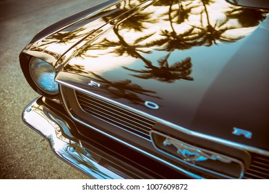 MIAMI - JANUARY 14, 2018: Palm tree silhouettes reflect on the hood of an antique Ford Mustang car parked on Ocean Drive.