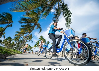 MIAMI - SEPTEMBER, 2018: A group of young tourists pass Citibikes, a brand that has enjoyed an exclusive bike-sharing agreement with Miami Beach since 2014