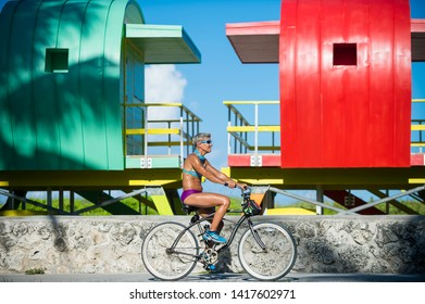 MIAMI - SEPTEMBER, 2018: A mature woman rides a bicycle past a row of brightly colored lifeguard towers awaiting placement on South Beach.
