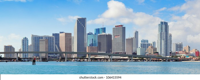 Miami skyscrapers with bridge over sea in the day.