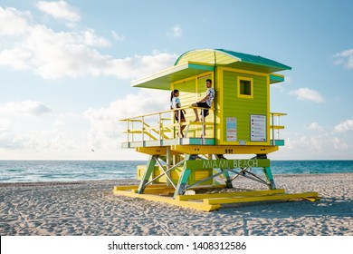Miami south beach, couple by lifeguard hut during Sunrise Miami Beach, men and woman on the beach