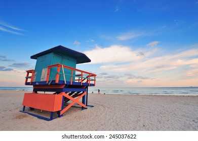 Miami South Beach sunset with lifeguard tower and coastline with colorful cloud and blue sky.