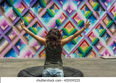 MIAMI, USA - APRIL 29, 2016: Young womans back with victory gesture at Wynwood Walls on APRIL 29, 2016 in Miami, USA.
