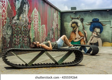 MIAMI, USA - APRIL 29, 2016: Young woman lied in a bench resting around art murals at Wynwood Walls on APRIL 29, 2016 in Miami, USA.
