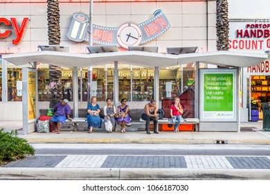 MIAMI, USA - AUG 18, 2014: people wait at a bus stop in front of a pharmacy shop. Public transportation in Miami is covered by busses which operate in 30 min frequency at the main road. een.