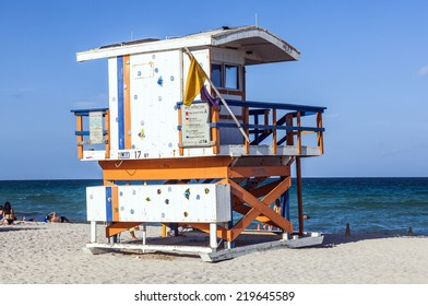 MIAMI, USA - AUG 23, 2014: People enjoy the beach next to a lifeguard tower in Miami, USA. South beach is famous for its wooden lifeguard towers which are designed in Art deco style.