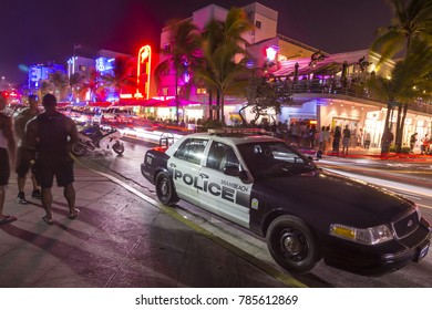 MIAMI, USA - Aug 30, 2014: police car parks at the Ocean Drive along South Beach Miami in the historic Art Deco District with hotels, restaurant and bar by night.